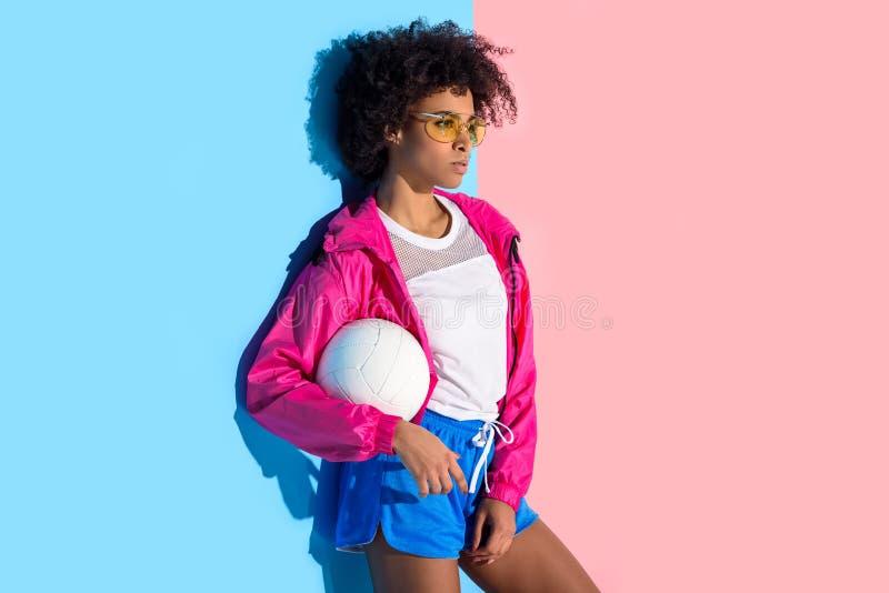 Moça nos vidros que guardam a bola e que olham afastado no rosa e no azul imagem de stock