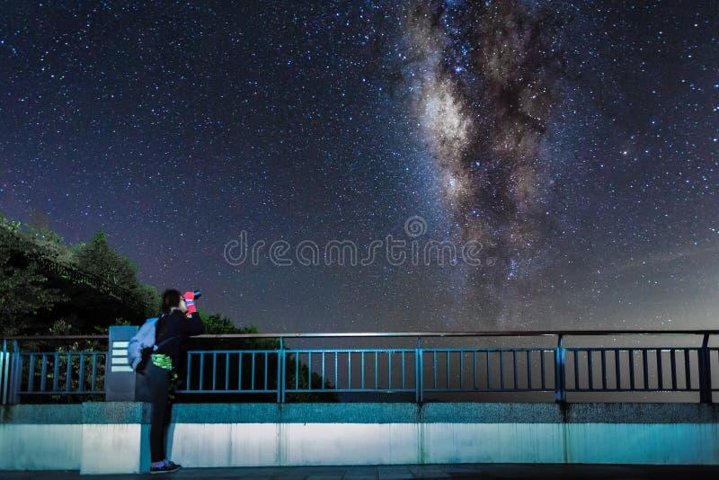 A moça olha acima na galáxia do céu noturno e da Via Látea com binocular fotografia de stock
