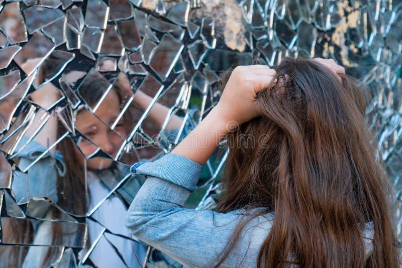 A moça olha em um espelho quebrado e sofre e mantém-se pelo cabelo O conceito de emoções humanas imagem de stock royalty free