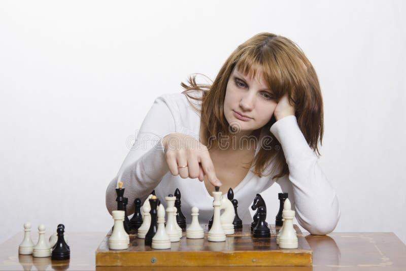 Moça para considerar um movimento durante o jogo de xadrez imagens de stock