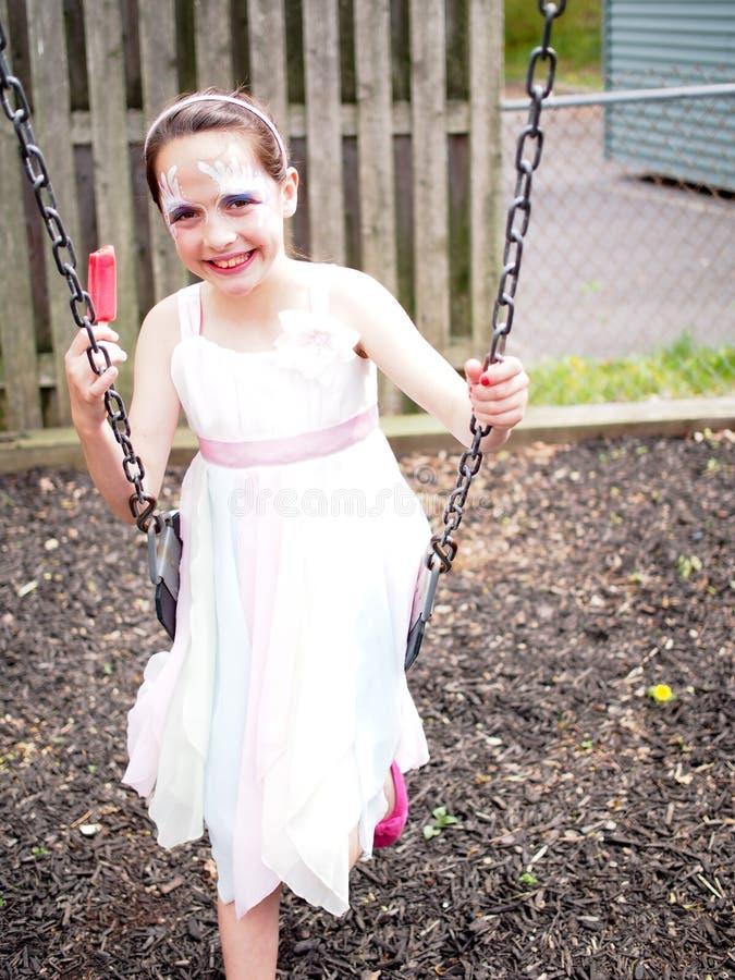 Moça pintada cara no balanço imagens de stock