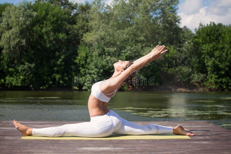 A moça pratica a ioga na costa do lago, o conceito de apreciar a privacidade e a concentração, luz solar fotos de stock