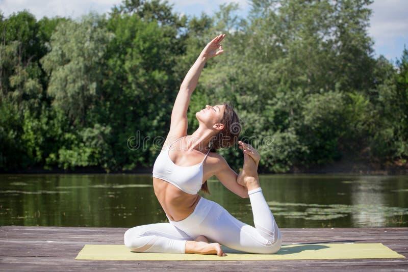 A moça pratica a ioga na costa do lago, o conceito de apreciar a privacidade e a concentração, luz solar fotografia de stock