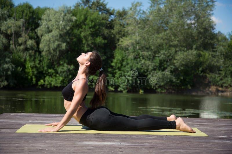 A moça pratica a ioga na costa do lago, o conceito de apreciar a privacidade e a concentração, luz solar imagem de stock
