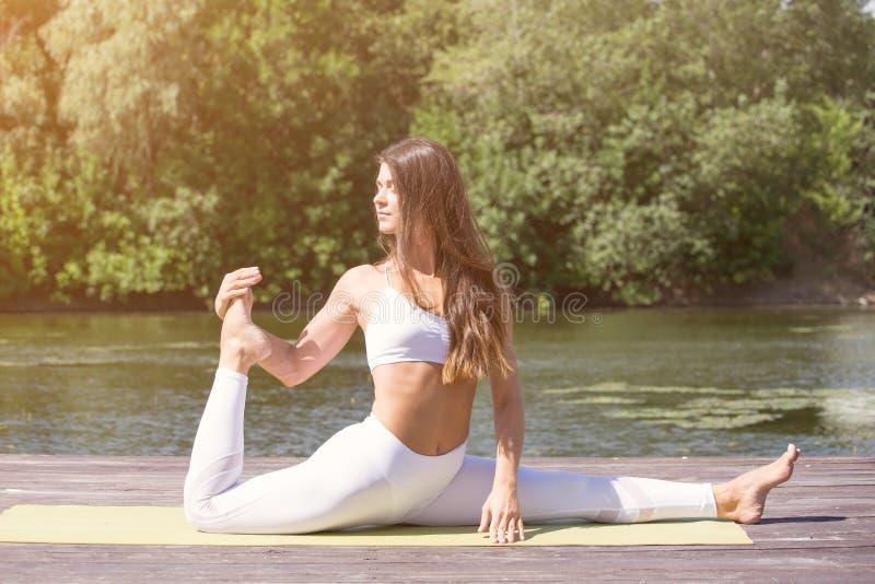 A moça pratica a ioga na costa do lago, o conceito de apreciar a privacidade e a concentração, luz solar foto de stock