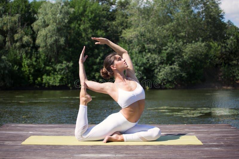 A moça pratica a ioga na costa do lago, o conceito de apreciar a privacidade e a concentração, luz solar fotos de stock royalty free