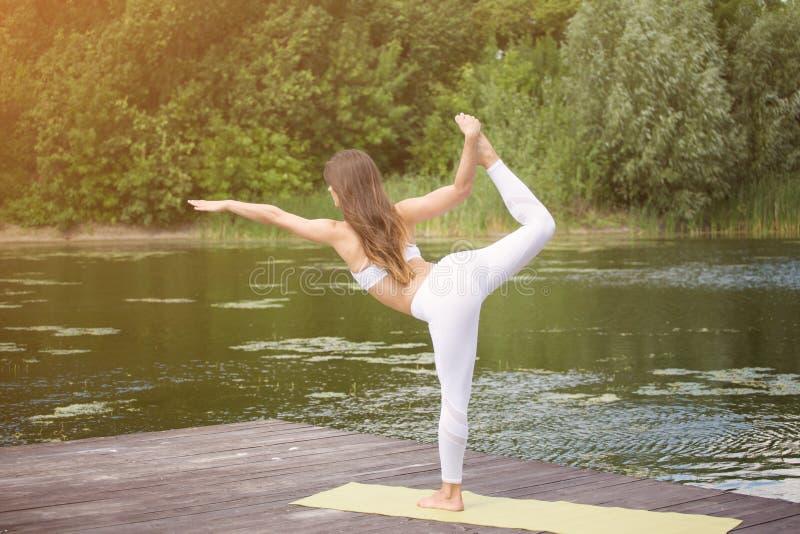 A moça pratica a ioga na costa do lago, o conceito de apreciar a privacidade e a concentração, luz solar foto de stock royalty free