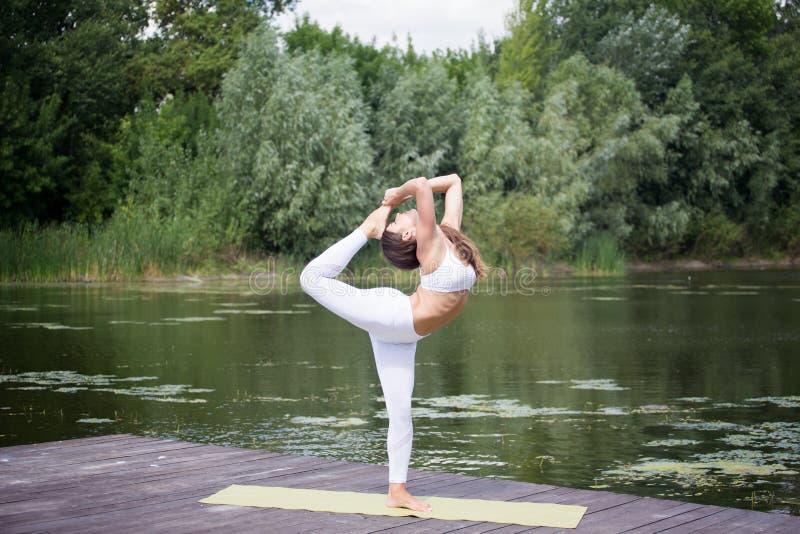 A moça pratica a ioga na costa do lago, o conceito de apreciar a privacidade e a concentração, luz solar imagem de stock royalty free