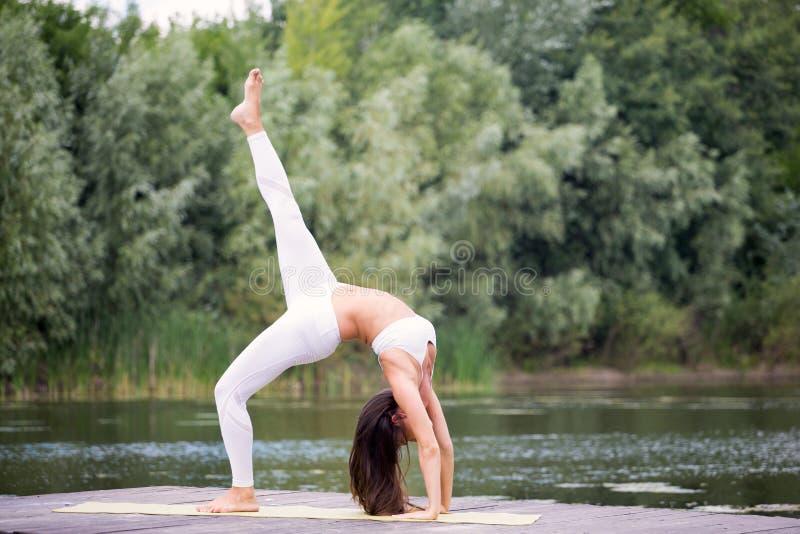 A moça pratica a ioga na costa do lago, o conceito de apreciar a privacidade e a concentração, luz solar fotografia de stock royalty free