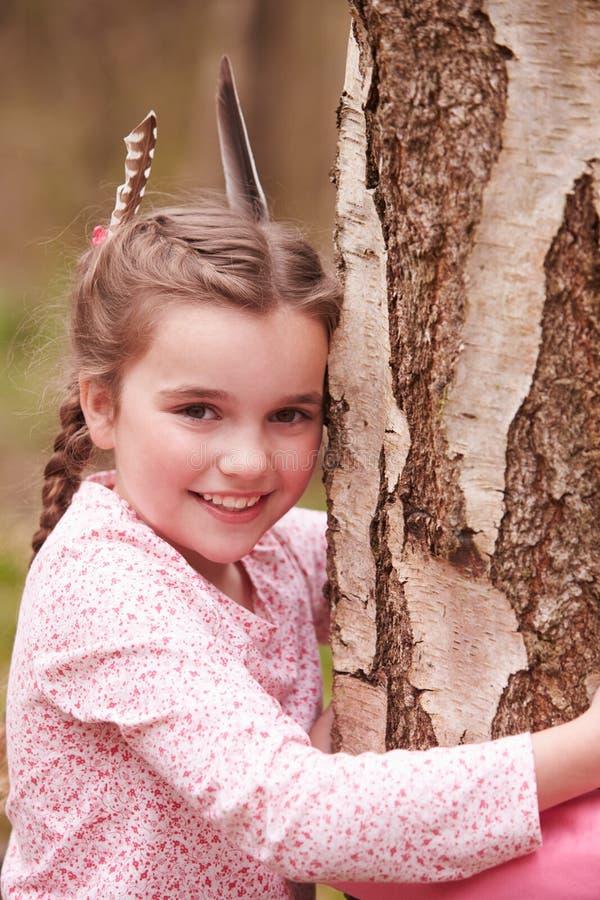 Moça que abraça a árvore na floresta imagens de stock