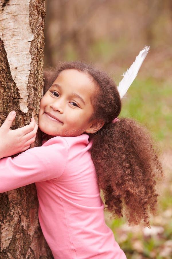 Moça que abraça a árvore na floresta foto de stock