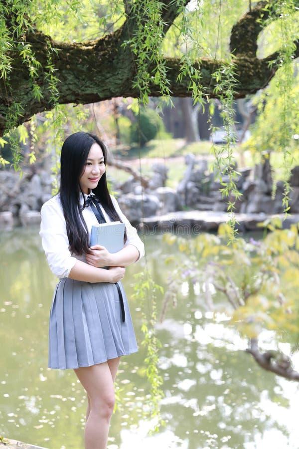 A moça que bonita bonita bonito feliz a estudante universitário da High School aprecia o tempo livre leu um livro por um lago no  imagem de stock