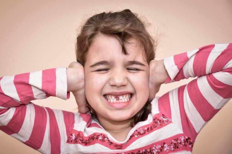 Moça que cobre suas orelhas imagens de stock royalty free