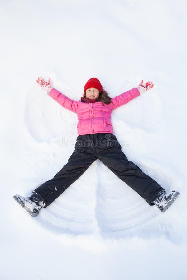 Moça que coloca na neve e que faz o anjo fotos de stock
