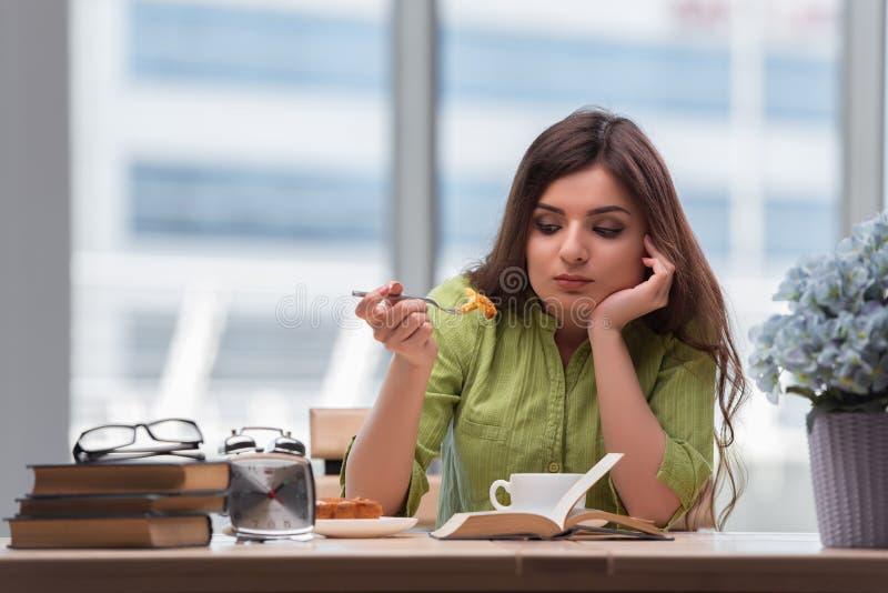 A moça que come o café da manhã em casa foto de stock
