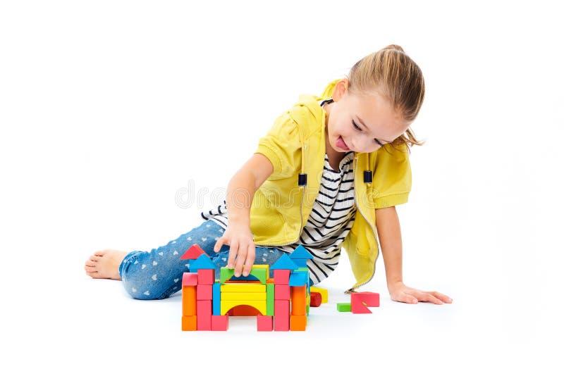 Moça que constrói um castelo com bloco de madeira do brinquedo Conceito da terapia da brincadeira no fundo branco fotos de stock