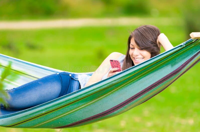 Moça que encontra-se em uma rede com telefone celular fotografia de stock