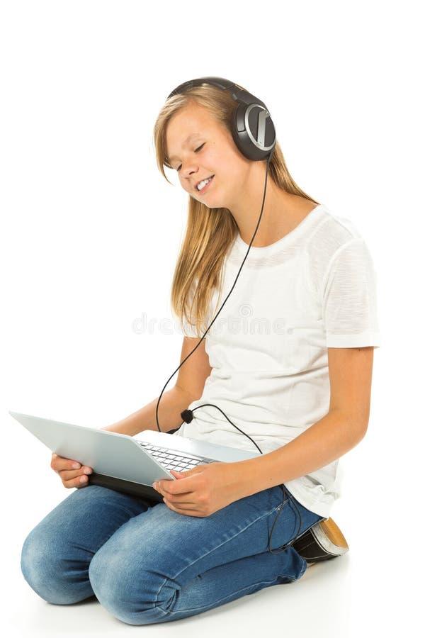 Moça que encontra-se no assoalho que escuta a música fotos de stock
