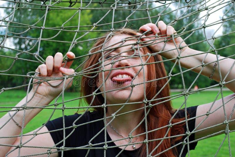 A moça que engana ao redor no campo de futebol perto da porta, mostra sua língua através da rede foto de stock royalty free