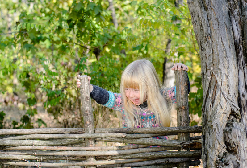 Moça que escala sobre a cerca de madeira imagens de stock