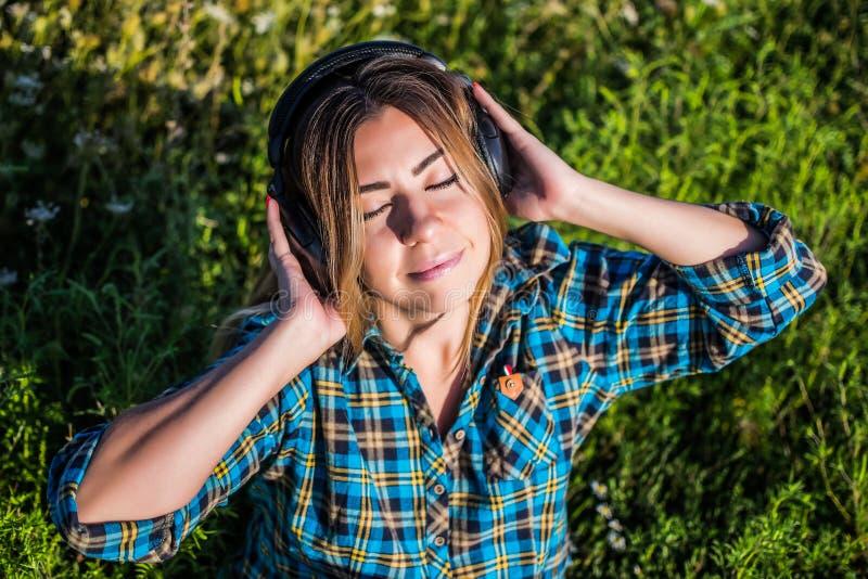 Moça que escuta o áudio em fones de ouvido pretos imagem de stock