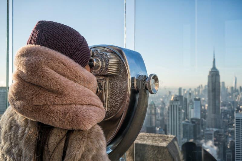 Moça que espreita através dos binóculos do turista com reflexão de New York City foto de stock