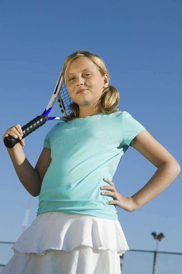 Moça que está no campo de tênis que guarda a opinião de baixo ângulo do retrato da raquete de tênis foto de stock