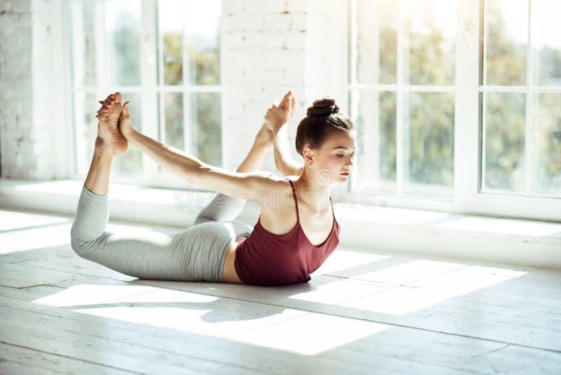Moça que estica sua espinha em uma postura da ioga imagens de stock royalty free