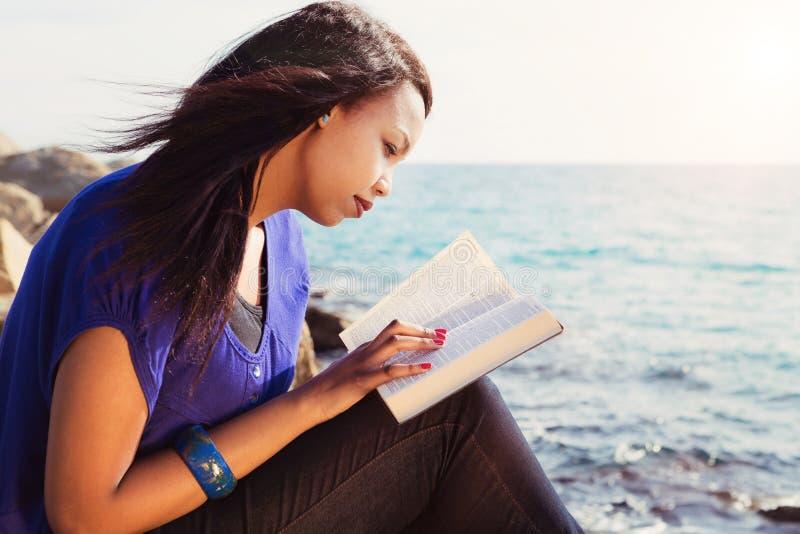 Moça que estuda sua Bíblia pelo mar fotos de stock royalty free