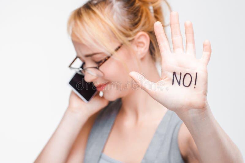 Moça que expressa a recusa, rotulando NÃO na palma fotografia de stock