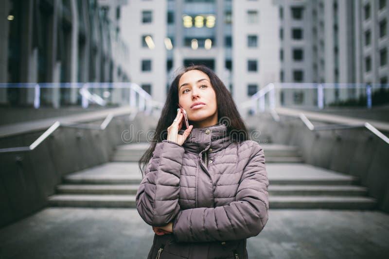 Moça que fala no telefone celular no centro de negócios do pátio a menina com cabelo escuro longo vestiu-se no revestimento do in imagem de stock royalty free