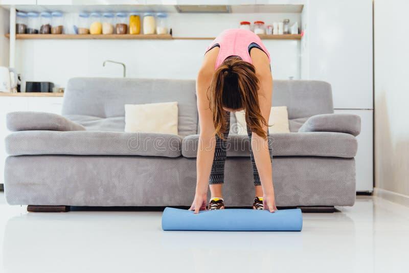 Moça que faz esticando meninas graciosas agradáveis do exercício com cabelo longo na meia-calça ocupada pela ioga em um tapete li foto de stock