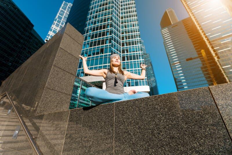 Moça que faz a ioga fora na cidade foto de stock