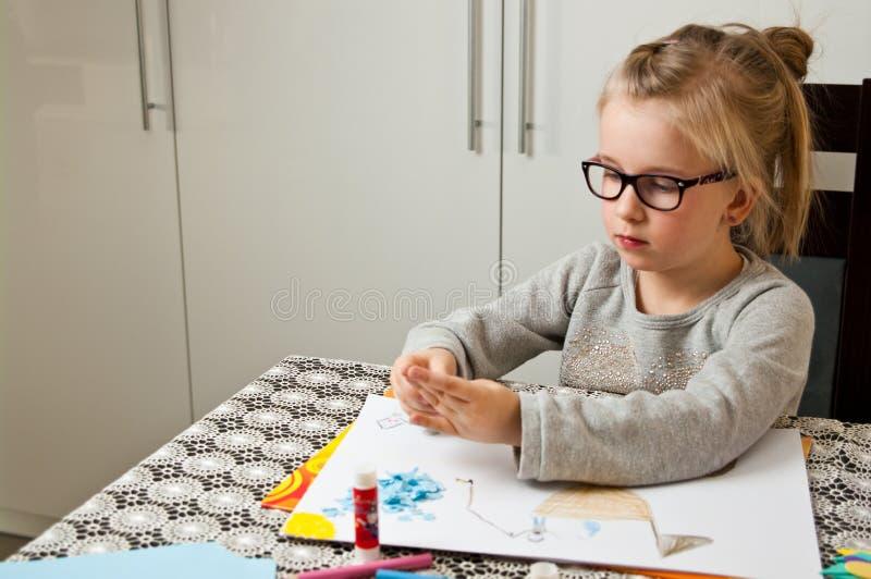 Moça que faz o trabalho de arte com papel fotografia de stock