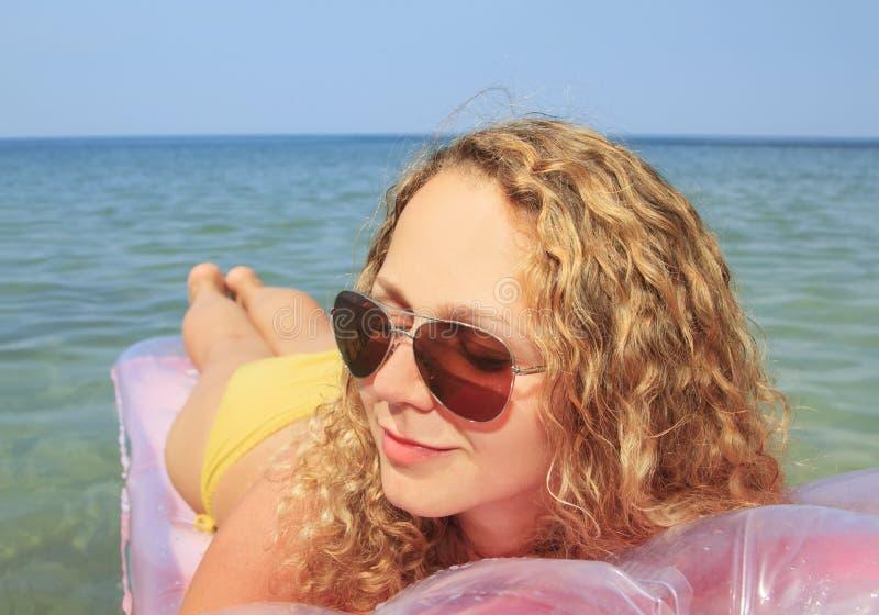Moça que flutua em um colchão no mar foto de stock