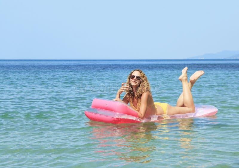 Moça que flutua em um colchão no mar fotografia de stock royalty free