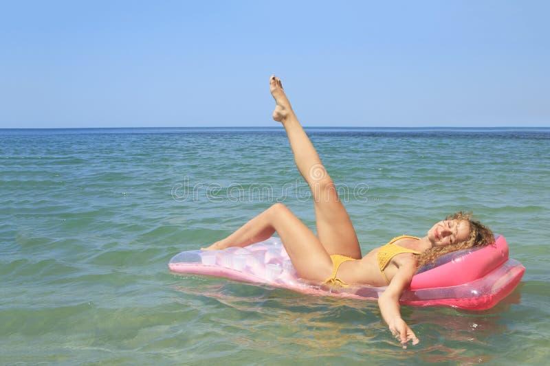 Moça que flutua em um colchão no mar imagens de stock royalty free