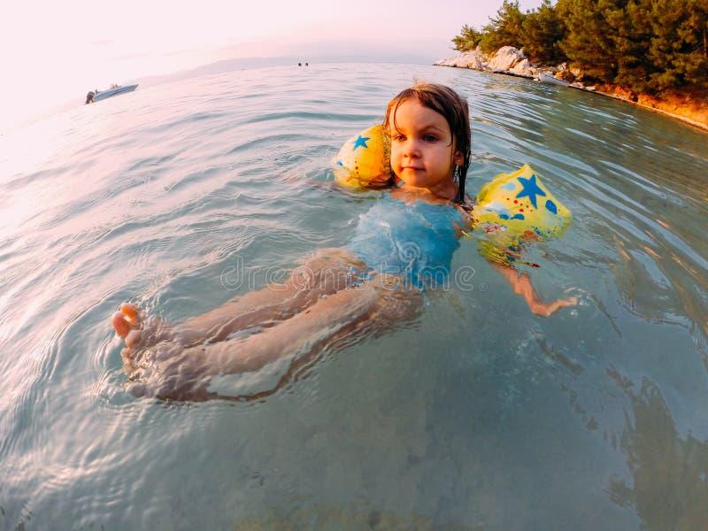 Moça que flutua na água pouco profunda imagem de stock