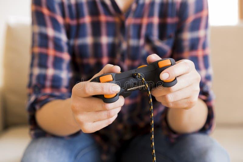Moça que guarda o manche ao jogar jogos de vídeo fotografia de stock royalty free