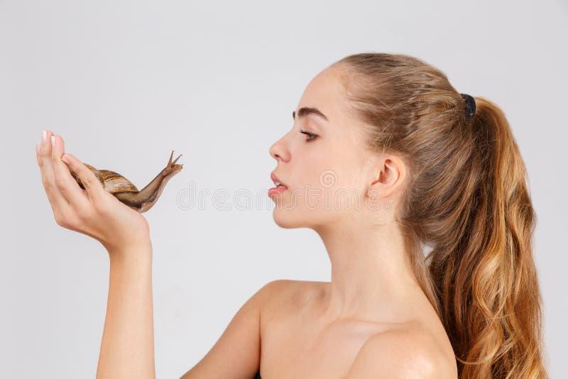 Moça que guarda um caracol grande de Ahatina e que olha o Isolado no branco fotografia de stock royalty free