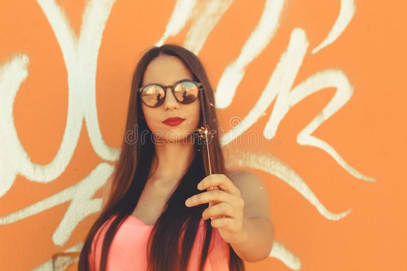 Moça que guarda um chuveirinho e que veste óculos de sol elegantes imagem de stock royalty free