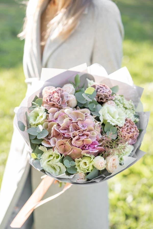 Moça que guarda um ramalhete bonito da mola arranjo de flor com as rosas da hortênsia e do jardim Alvorecer ou por do sol brilhan foto de stock royalty free