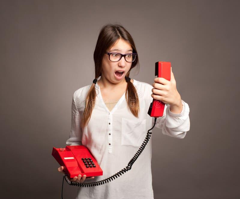 Moça que guarda um telefone fotografia de stock