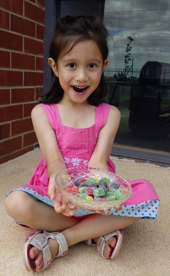 Moça que guarda uma bacia de Lollies. foto de stock royalty free