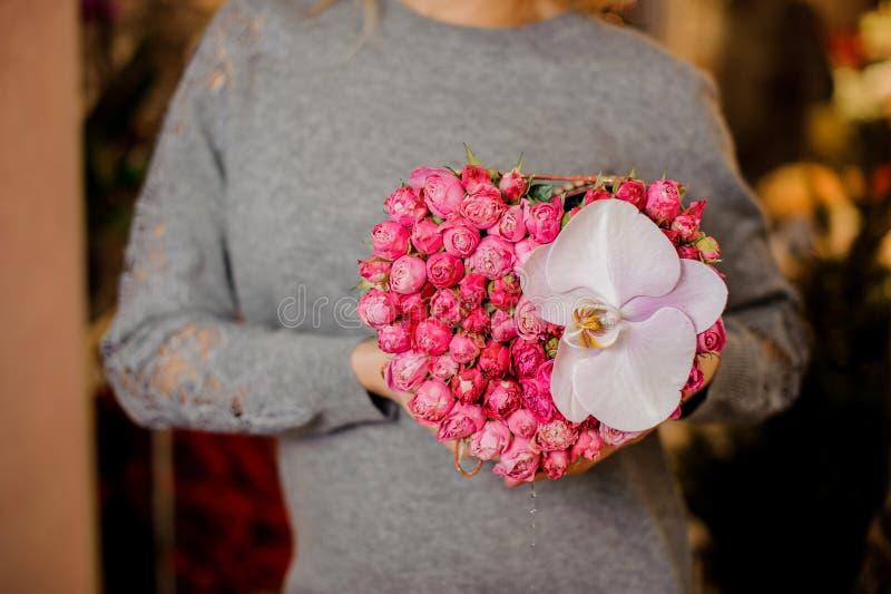 Moça que guarda uma caixa de presente de rosas cor-de-rosa pequenas e de orquídea grande imagem de stock