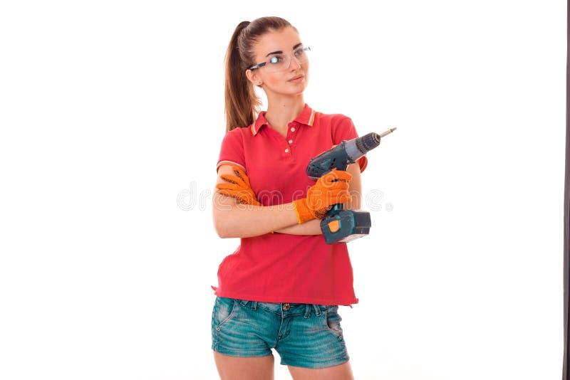 Moça que guarda uma ferramenta para o reparo dos apartamentos nos óculos de proteção e na camisa vermelha imagem de stock