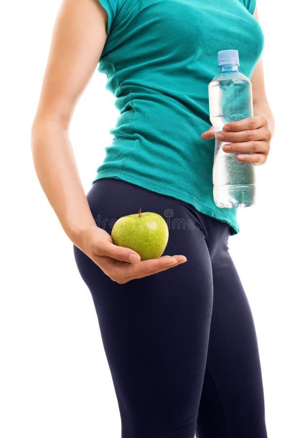 Moça que guarda uma maçã e uma garrafa da água fotos de stock royalty free