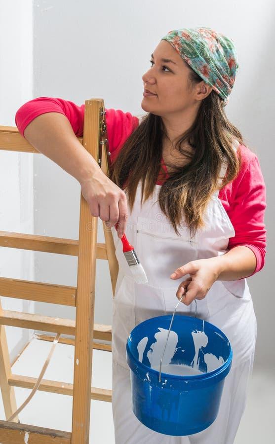 Moça que inclina-se em uma escada pronta para pintar paredes imagem de stock royalty free