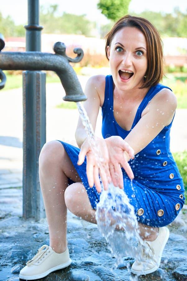 A moça que joga com água esguincha e fazer espirra imagem de stock