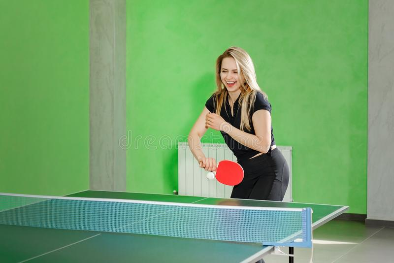 Moça que joga o pong do sibilo o atleta retrocede a bola com uma raquete de tênis imagens de stock royalty free